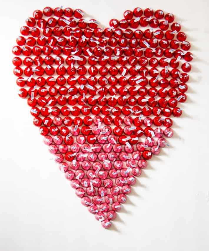 Red heart made with foil wrapped chocolates on white background.