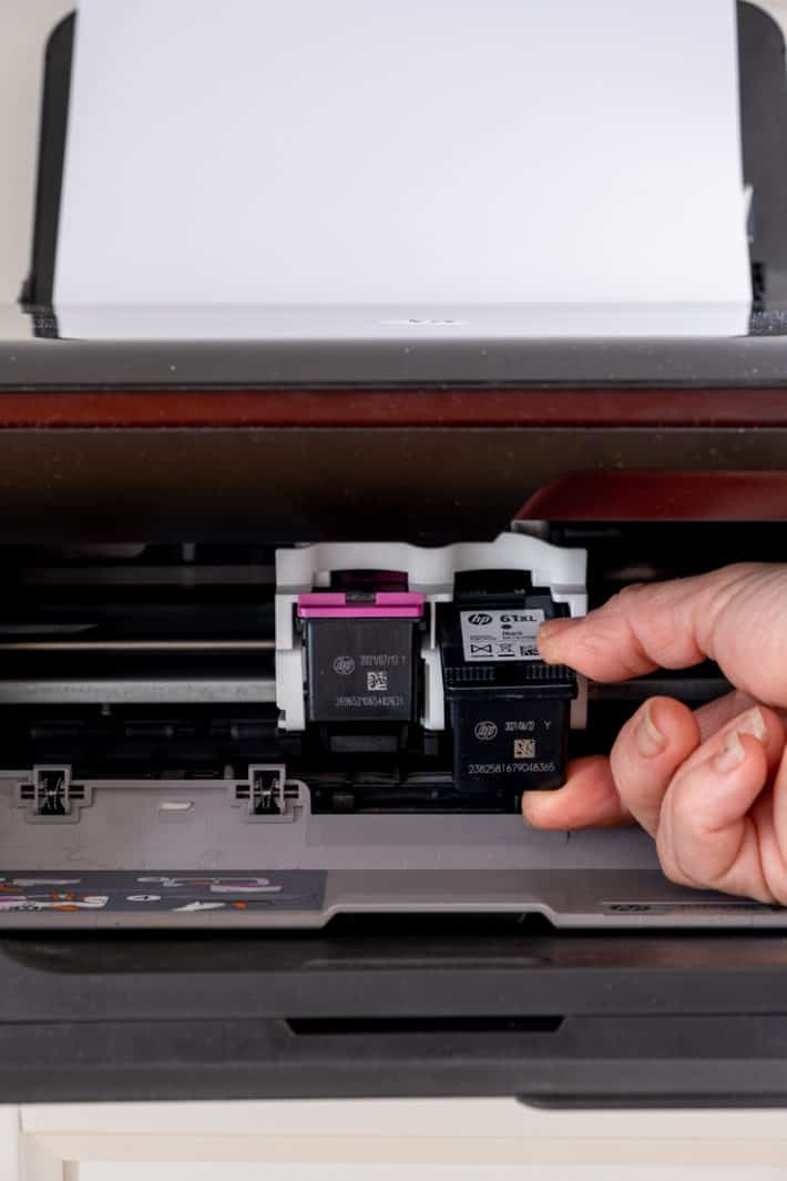 Hand removing black printer cartridge in inkjet printer.
