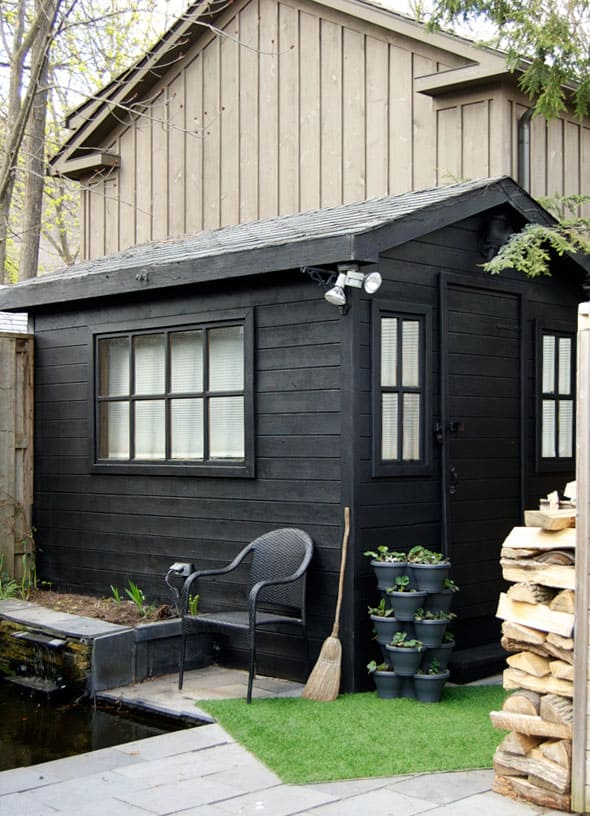 Black painted shed in slate backyard.