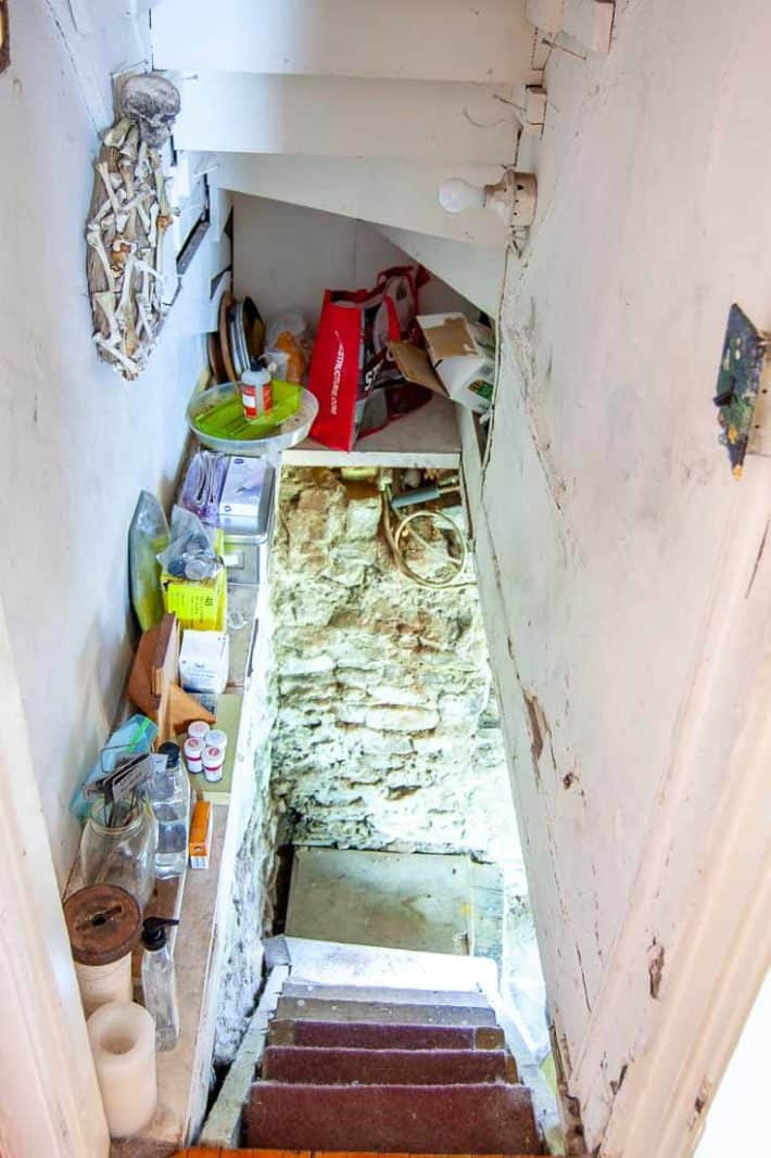 Creepy basement stairs leading down with a cluttered shelf on the side and rubble wall visible at the bottom.