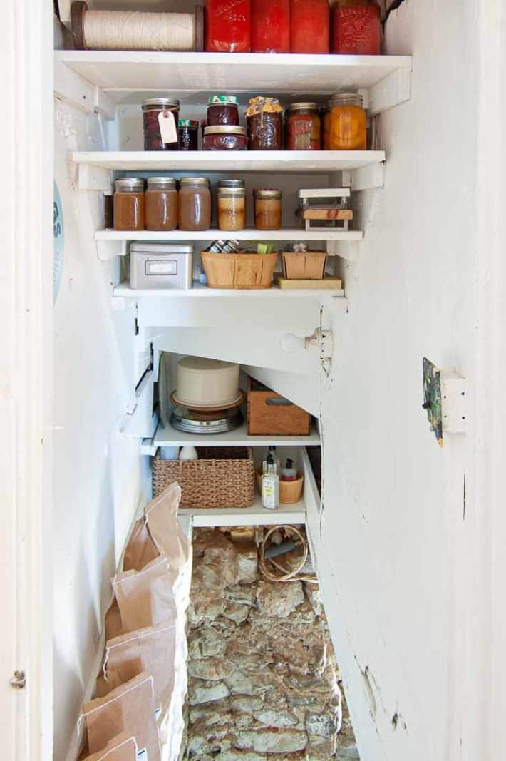 Shelves under stairs providing storage for canned goods and colourful preserves like tomatoes and peaches.
