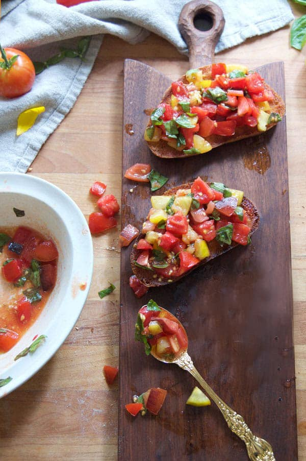 Bruschetta topped fried bread sits on a wood cutting board.