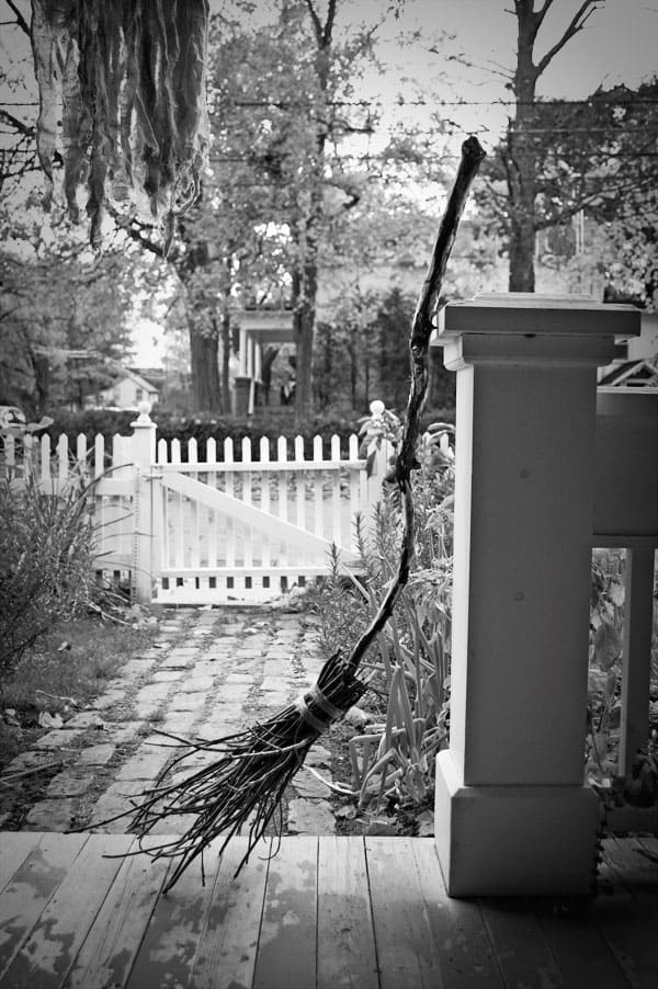 Eerie black and white photo of a broom resting on an old porch.