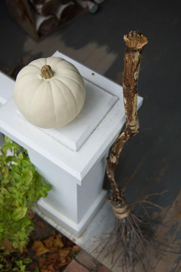 A homemade witches broom rests against a white pillar on an old porch.