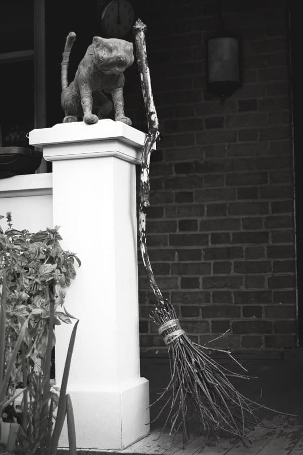 A (fake) mummified cat sits on top of a porch pillar with a witches broom beside it.
