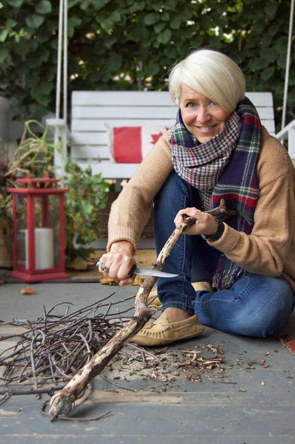 Karen Bertelsen carves a stick with a buck knife.