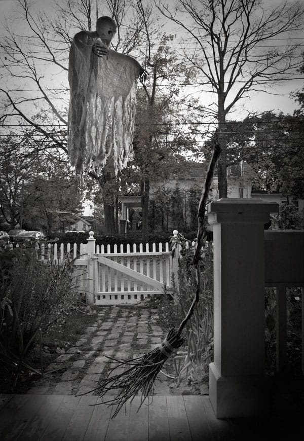 Creepy black and white photo of a witches broom and floating skeleton on a porch with leafless trees in the background.