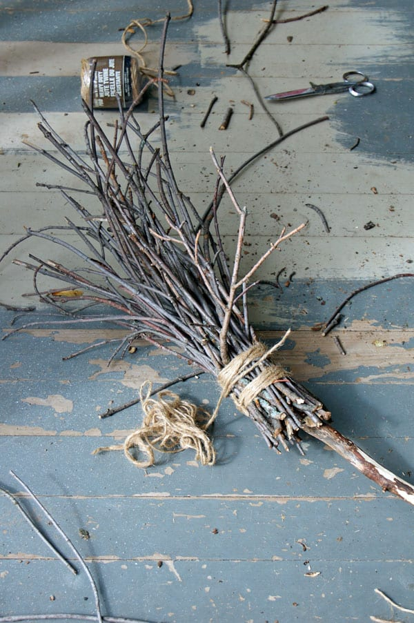 A witches broom partly finished, laying on a porch with peeling paint.