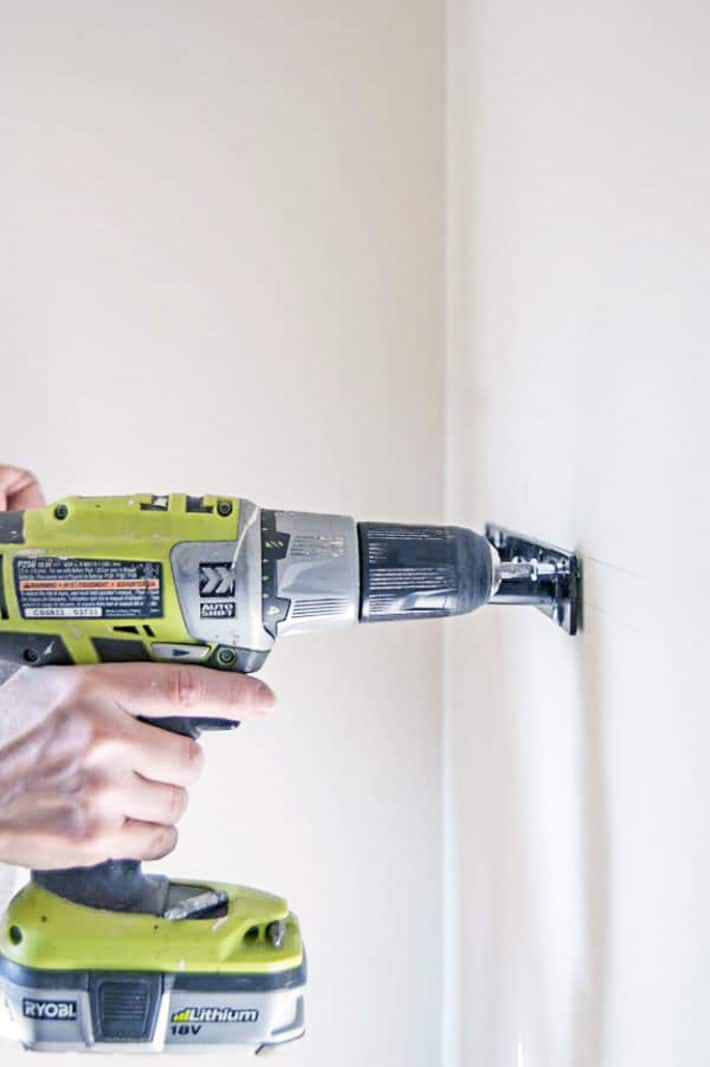 Securing a bracket to a wall using molly bolts and a bright green Ryobi cordless drill.