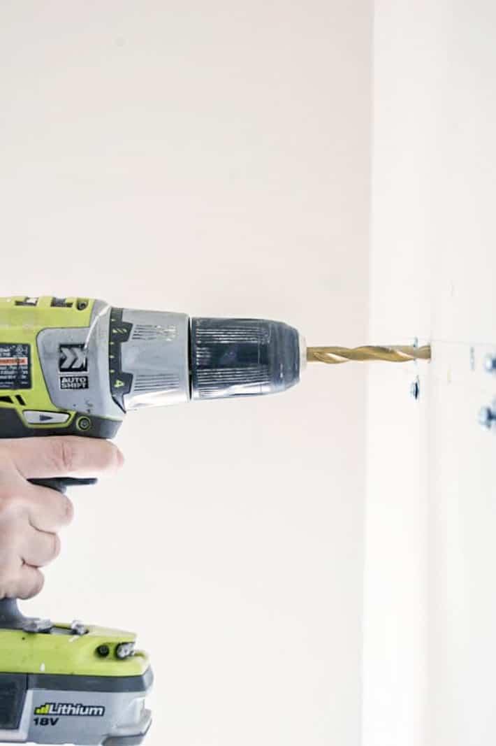 Bright green Ryobi drill, drilling into white wall.