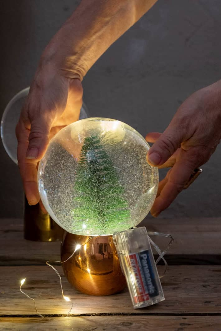 Lighting up a snow globe with copper wire lights.