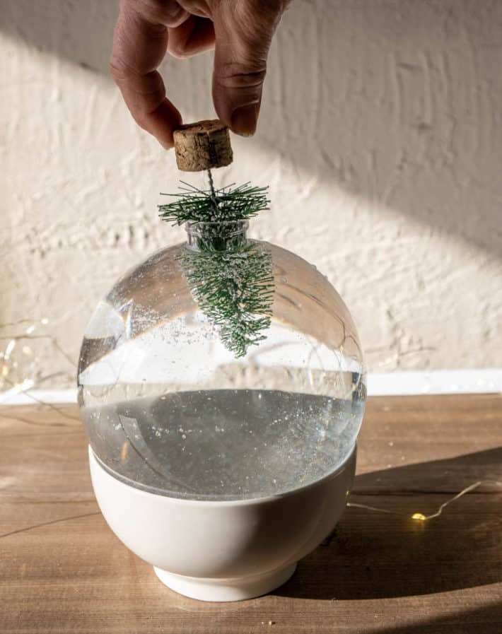 Pushing a bottle brush tree into a plastic Christmas ball, making a snow globe.