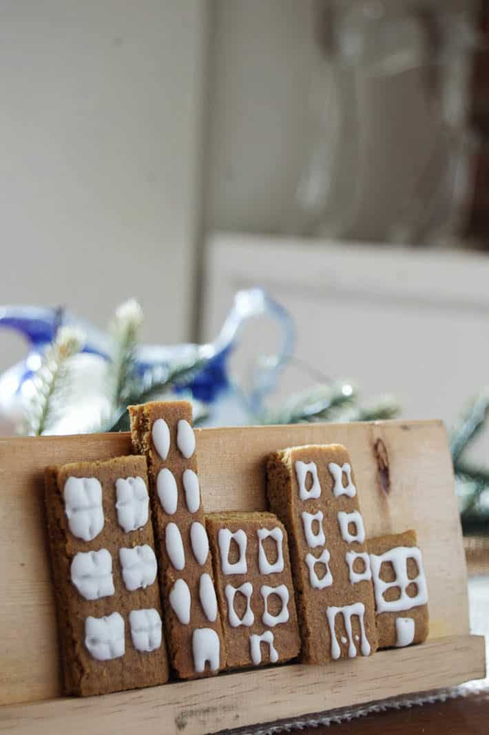 Gingerbread condos sit on a cookie display stand.