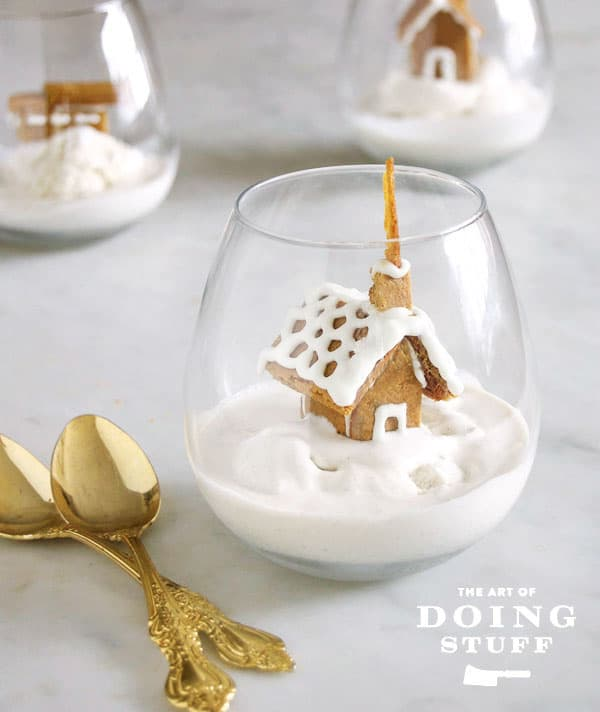 Tiny gingerbread church in a clear glass on a bed of vanilla ice cream for an easy Christmas dessert.