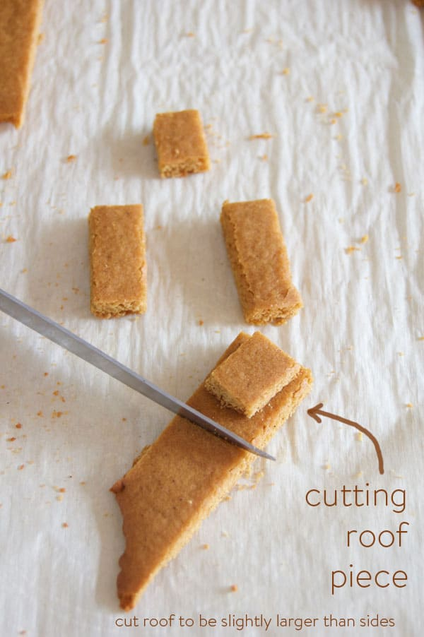 Cutting a piece of gingerbread roof with a paring knife on parchment paper.