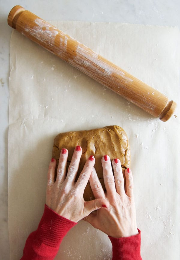 Pressing out gingerbread dough onto a sheet of parchment paper with floured hands and rolling pin.