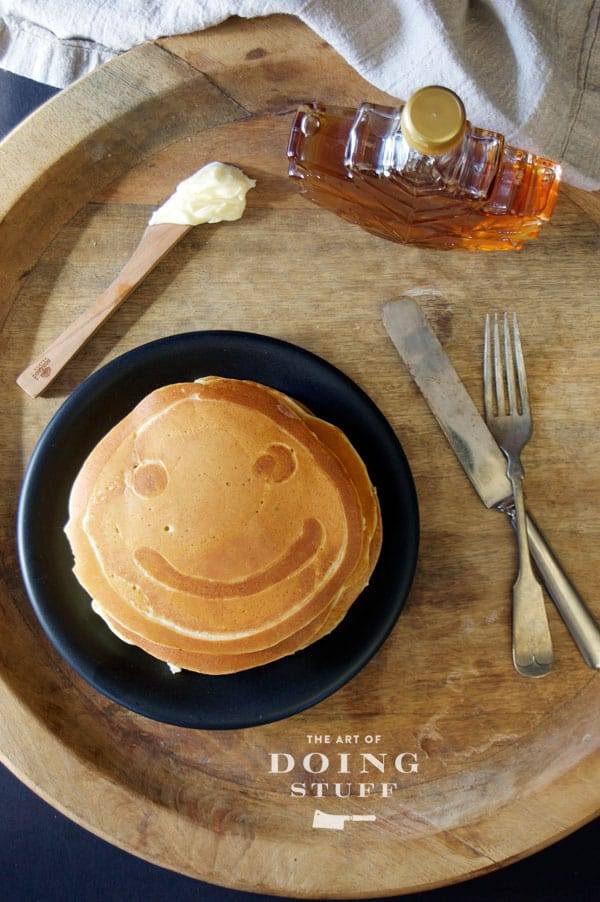 Overhead shot of a pancake featuring a smiley face, on a black plate on a round wood serving tray.