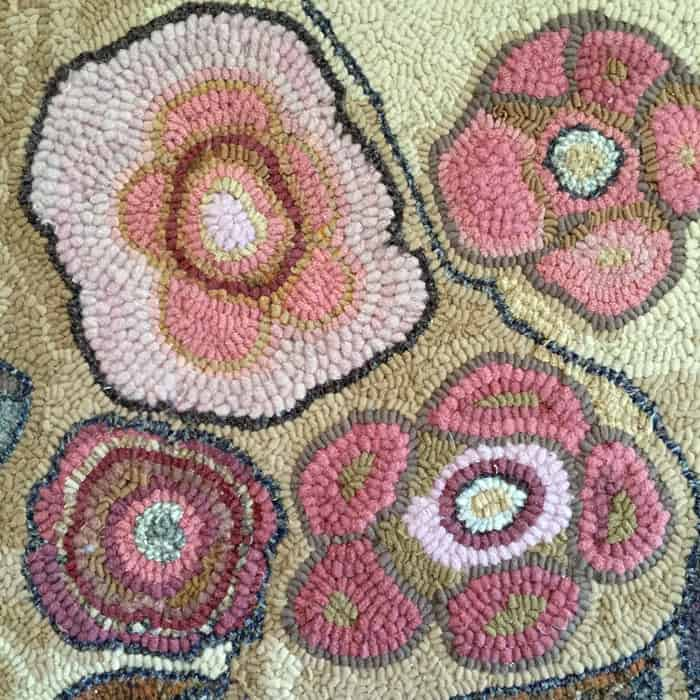 Abstract flowers in traditional rug hooking.