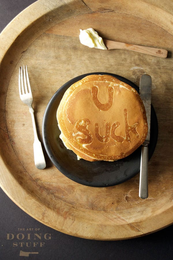 Overhead shot of stack of pancakes on a black plate, with U Suck written on the top pancake. All set on round wood serving tray with a wooden spoon slathered in butter.