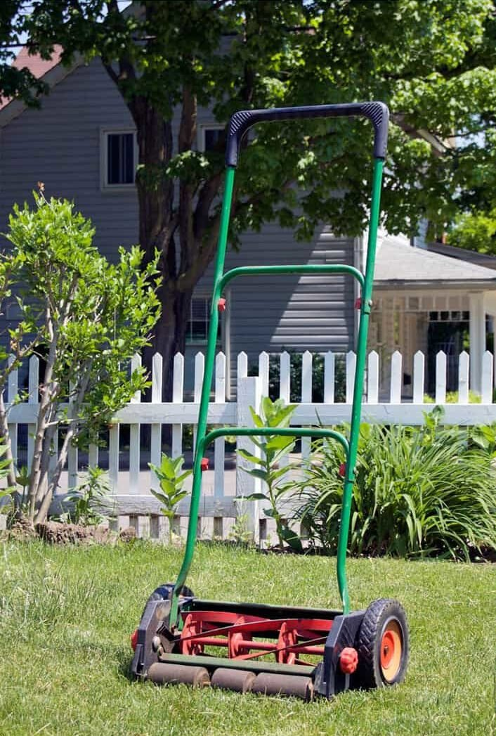 Push mower standing on lawn with white picket fence in background