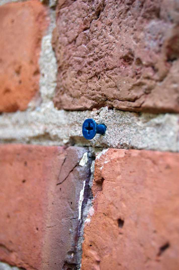 A tapcon screwed into the mortar of a brick wall.