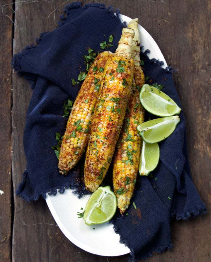 grilled corn on the cob with cilantro and lime on a platter.