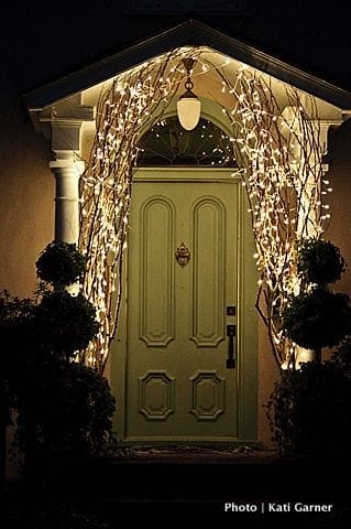 A green front door is flanked by large willowy branches covered in twinkle lights in the shape of an arch at Christamas.