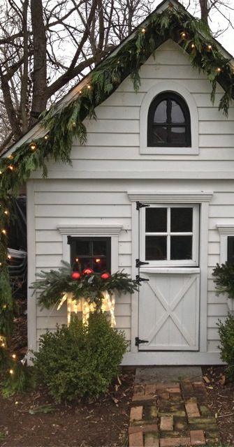 A small white outbuilding with a dutch door and brick path leading up to it is decorated with live garland and white twinkle lights.