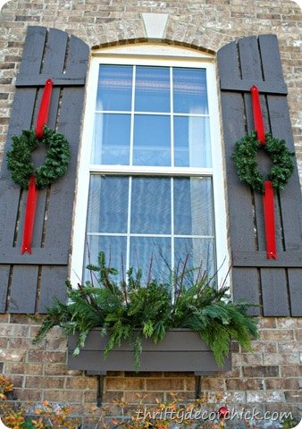 An exterior window flanked by black wood shutters with small wreaths hanging from red ribbon on each.