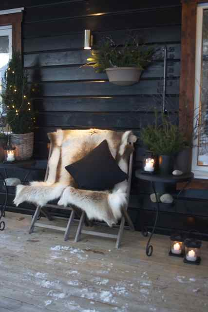 A very nordic looking front porch on a black wood sided house shows two folding wood chairs covered in fur with a black throw pillow.