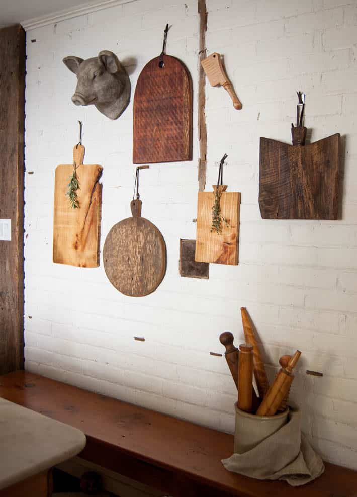 5 wood DIY meat and cheese platters hanging on a white painted brick wall.