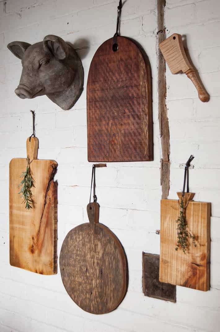 Handmade charcuterie boards hanging on painted brick wall.