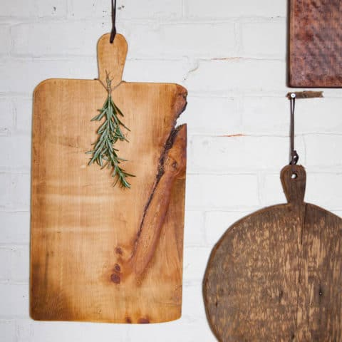 Handmade Wood cheese boards hanging on brick wall.