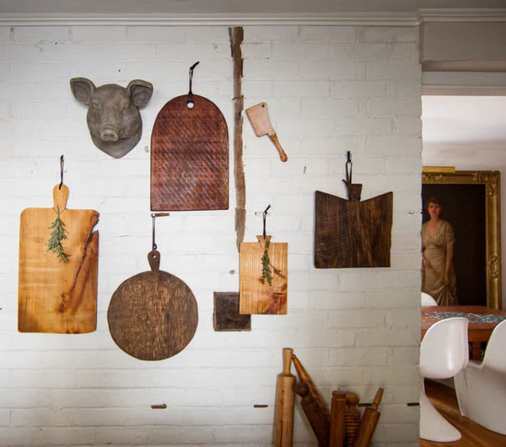 Various shapes and sizes of DIY charcuterie boards hanging on white brick wall.