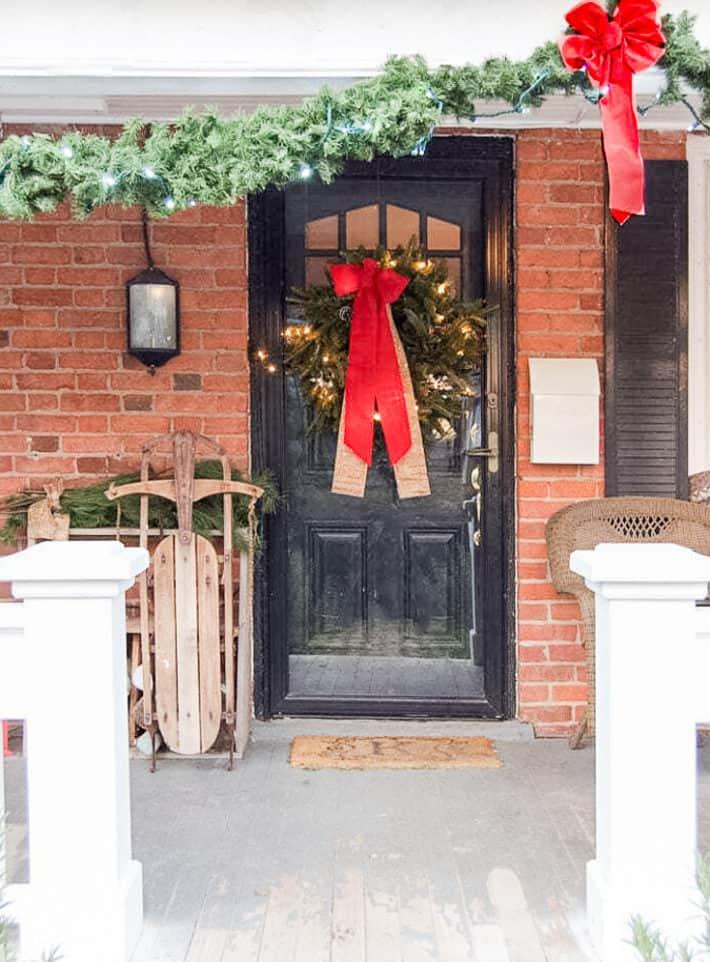 An antique wood sleigh sits beside a black front door on a red brick house decorate with a simple evergreen wreath with a large red bow.