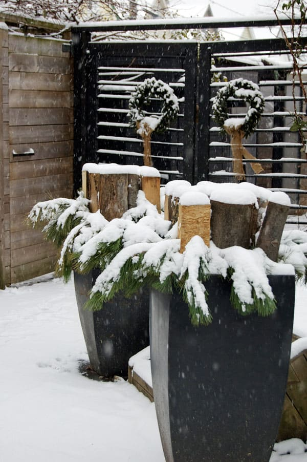 Christmas planters with evergreen branches surrounding small stacks of wood in each.