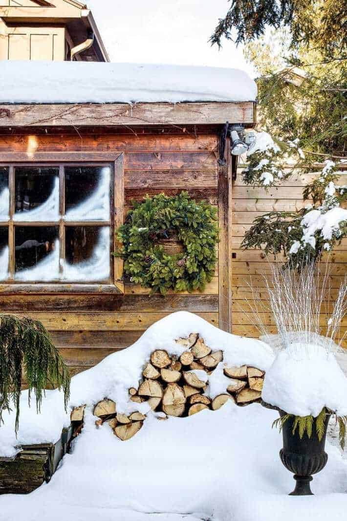 A cedar shed with an evergreen wreath hanging above a large stack of snow covered wood.