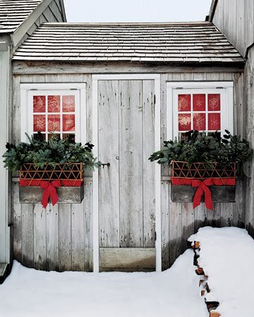 A silvery wood shed door flanked by two windows lined with red paper and accented by evergreen filled window boxes with red ribbon..
