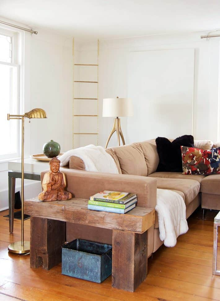 Ecclectic, cozy, white living room with gold chain and dowel magazine rack hanging from the ceiling.