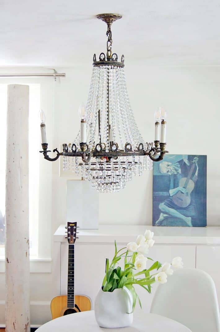 Completely white room with modern furnishings and an antique, crystal chandelier hanging from the ceiling.