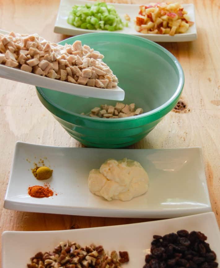 Dice ingredients laid out mise en place, with diced chicken being added to green bowl