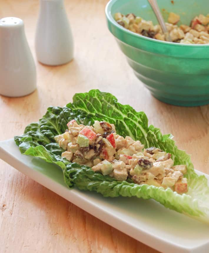Chicken salad bright with apples celery and raisins, served on a crisp lettuce leaf on a white plate.