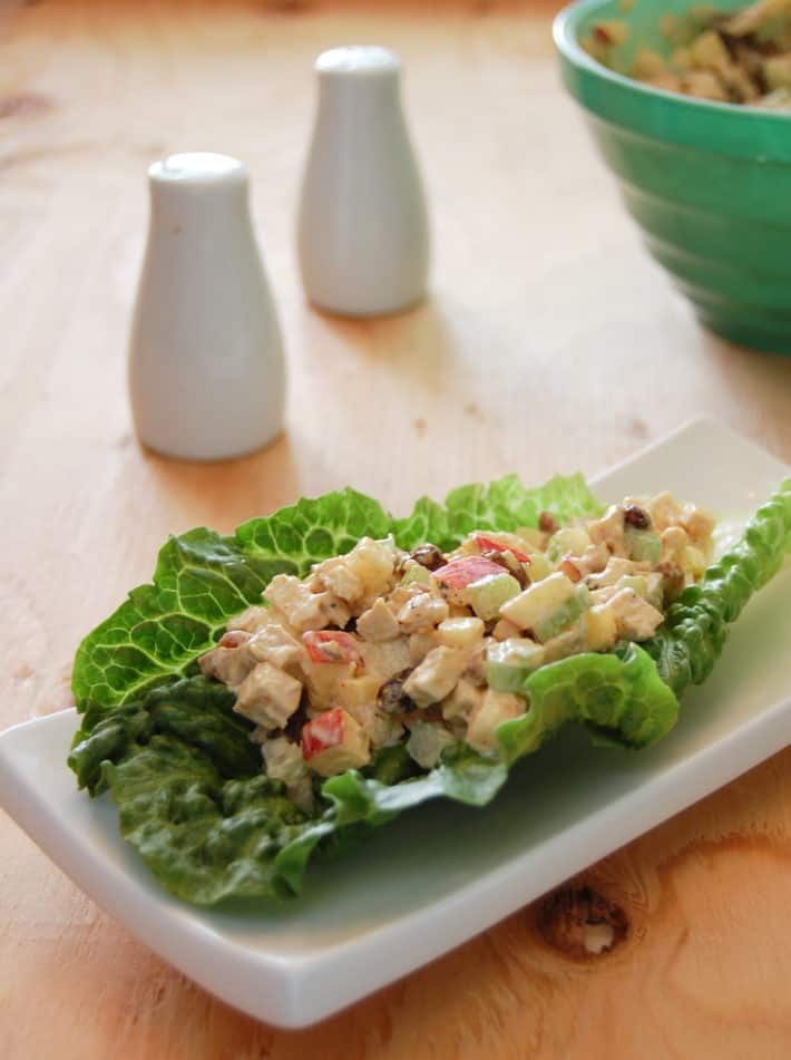 Curry chicken salad with apples and pecans served on a romaine lettuce leaf on a small white rectangular plate.