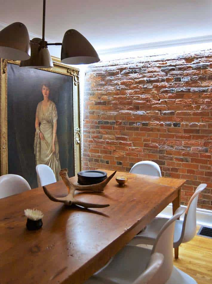Dining room with brick wall illuminated by LED strip lighting.