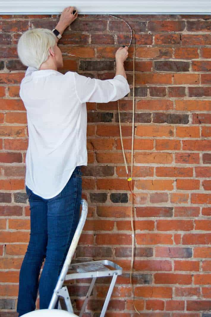 Woman installing strip lights under crown moulding to illuminate brick wall.