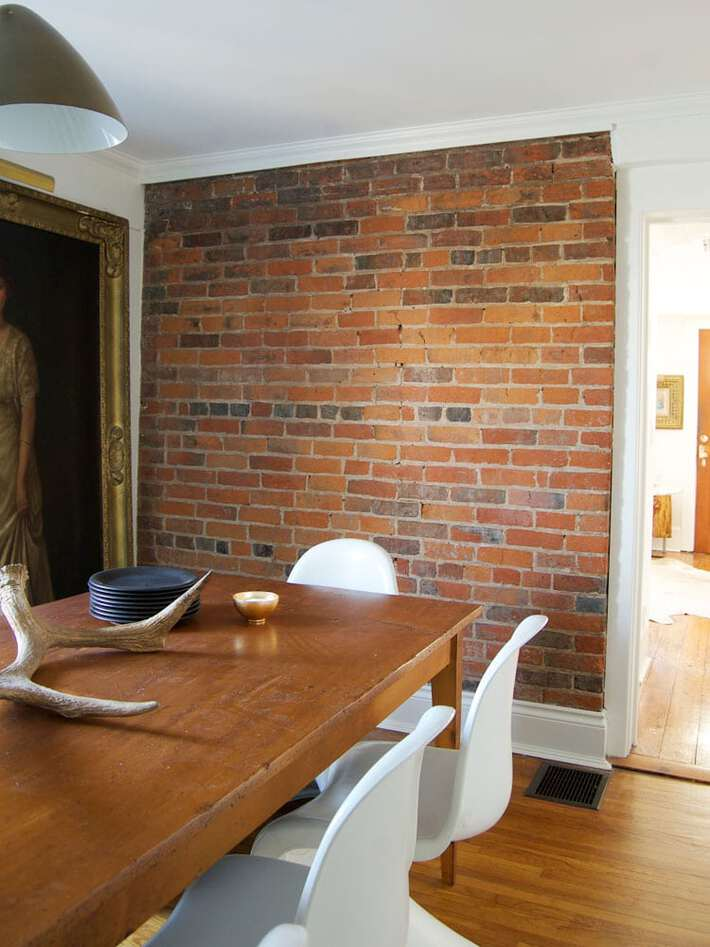 Dining room with a brick wall, harvest table and modern white chairs.