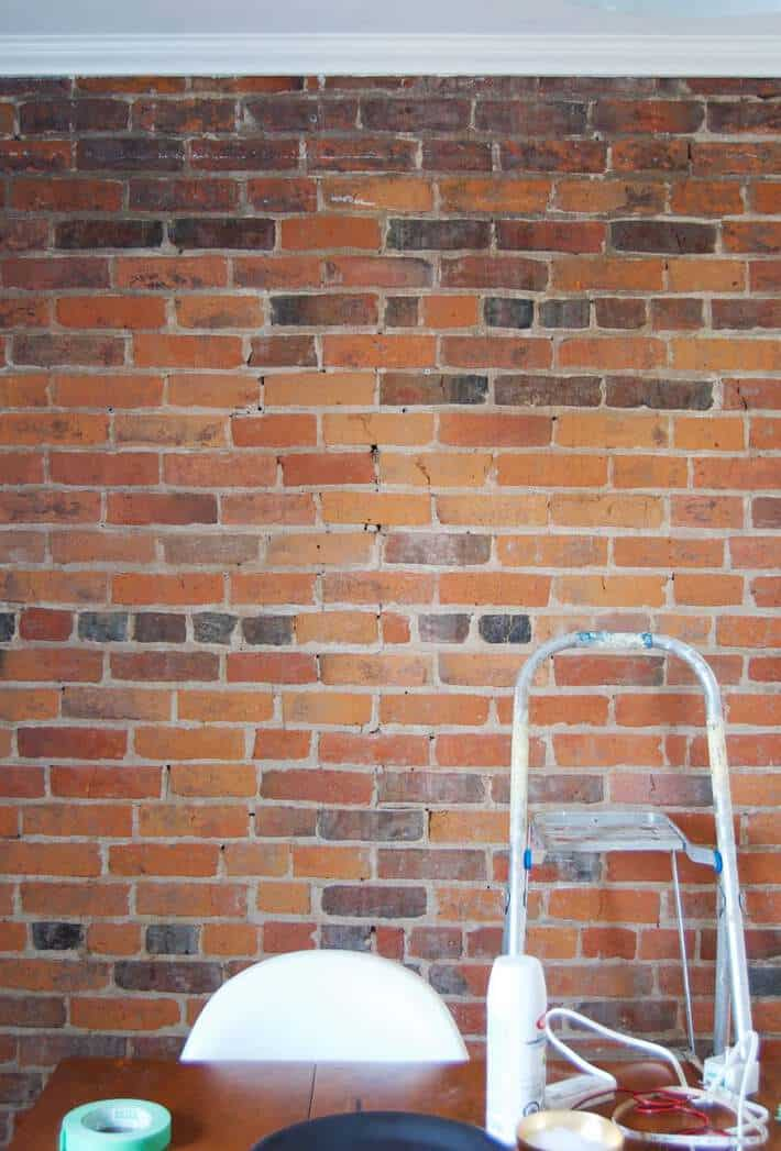 Plain brick wall with a step ladder in front of it prior to installing LED lights.