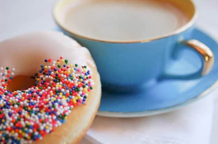 A glazed donut covered in multi-colored sprinkles sits beside a blue teacup.