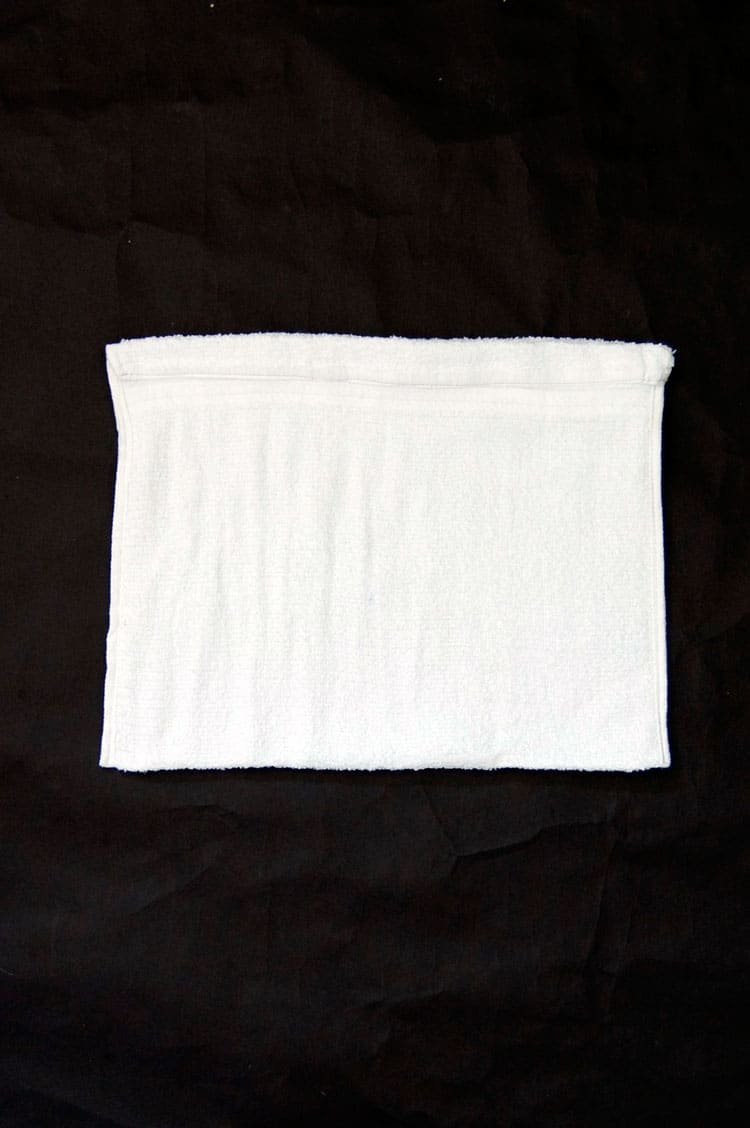 White towel with sides sewn up and top rolled down to make a casing for string or ribbon.