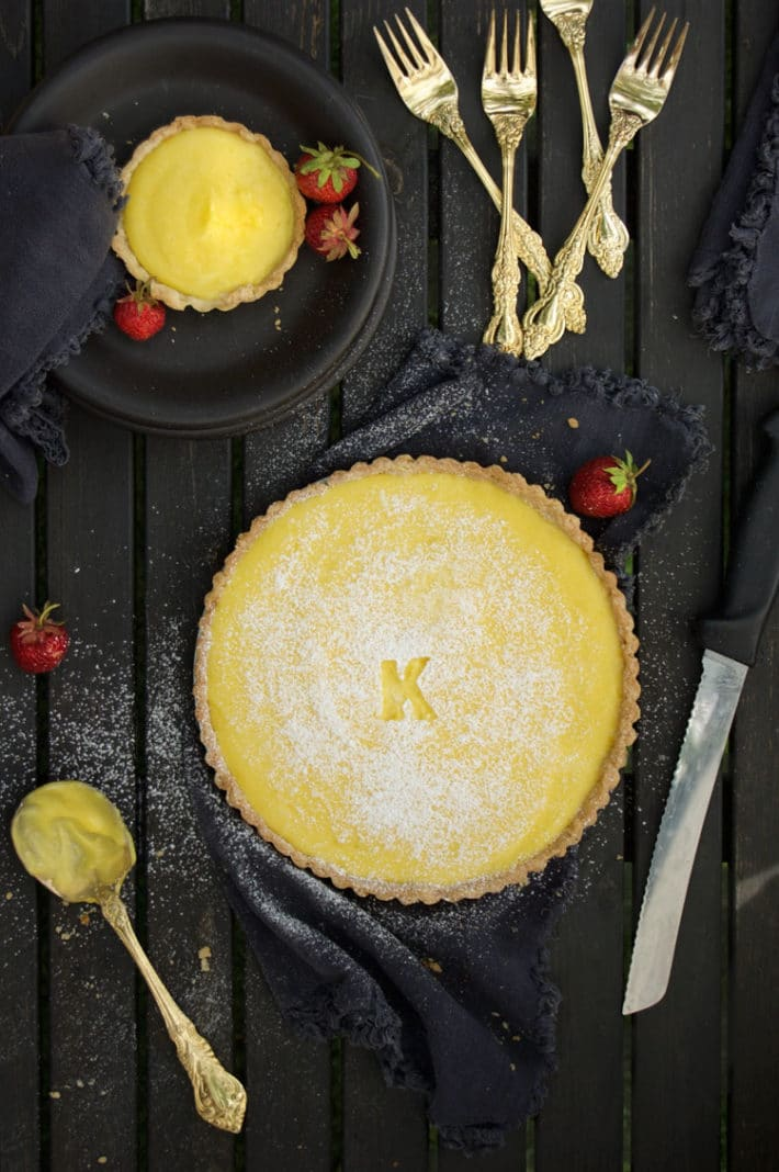 A lemon tart sprinkled with powdered sugar on a black table surrounded by gold flat wear, black napkins and bright red strawberries.